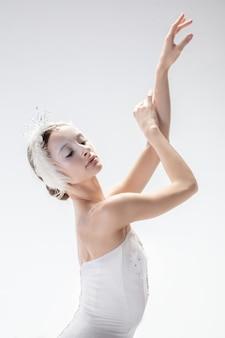 Молодая изящная балерина на фоне белой студии