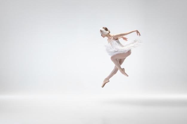 Young graceful ballerina on white studio background