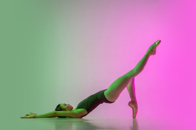 Young and graceful ballet dancer isolated on gradient pink-green