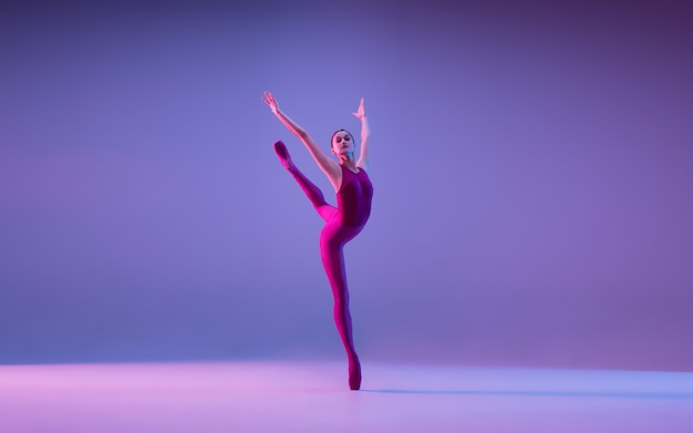 Young and graceful ballet dancer isolated on purple studio background in neon light