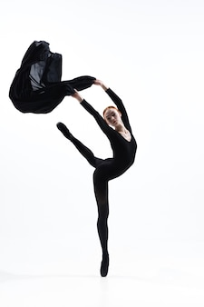 Young and graceful ballet dancer in minimal black style isolated on white studio background. art, motion, action, flexibility, inspiration concept.