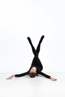 Young and graceful ballet dancer in minimal black style isolated on white studio background.