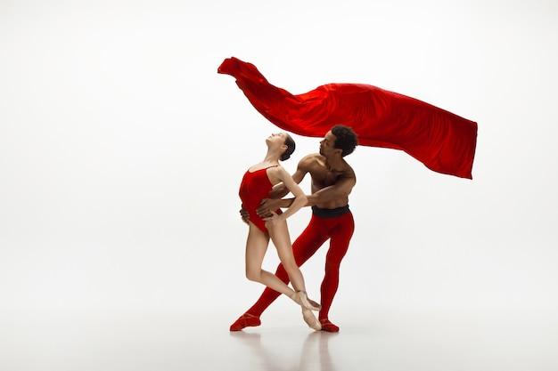Giovane coppia graziosa di ballerini che ballano sul fondo bianco dello studio