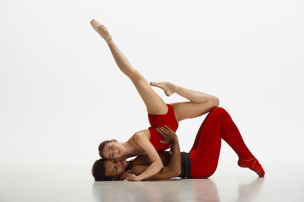 白いスタジオの背景で踊るバレエダンサーの若い優雅なカップル