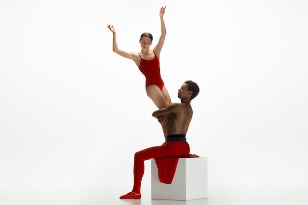 Молодая изящная пара артистов балета танцует на фоне белой студии