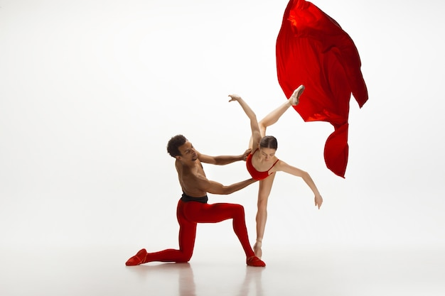 흰색 스튜디오 배경에서 춤을 추는 우아한 젊은 발레 댄서