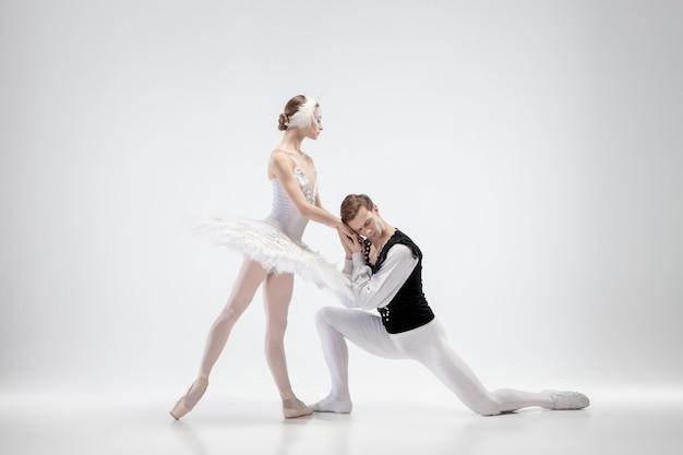 白いスタジオの背景にバレエダンサーの若い優雅なカップル