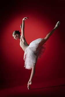 Young graceful female ballet dancer or classic ballerina dancing at red studio.