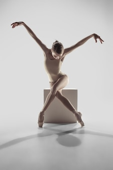Young graceful female ballet dancer or classic ballerina dancing on white studio.