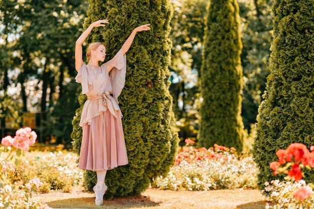 Молодая изящная женская балерина в театральном платье, позирующем в солнечном парке.