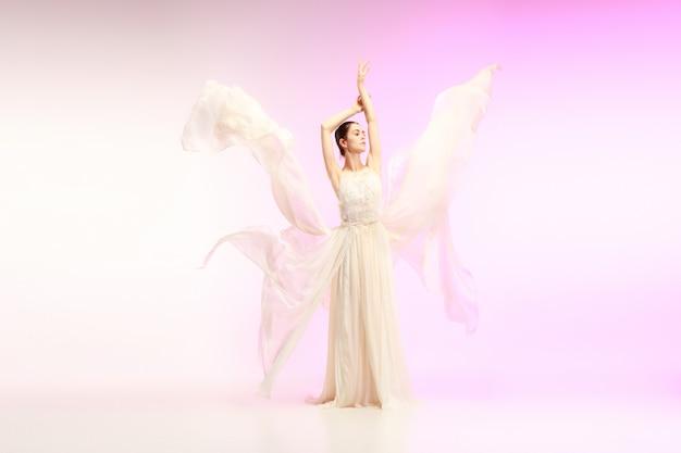 젊고 우아한 여성 발레 댄서나 분홍색 스튜디오에서 춤을 추는 클래식 발레리나. 뾰족한 신발에 백인 모델