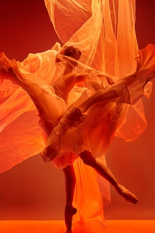 ピンクのスタジオで踊る若い優雅な女性のバレエダンサーまたは古典的なバレリーナ