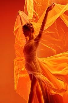 Молодая изящная балерина или классическая балерина танцует в розовом