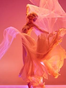 젊고 우아한 여성 발레 댄서나 빨간 스튜디오에서 춤을 추는 클래식 발레리나. 뾰족한 신발에 백인 모델
