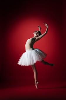 Молодая изящная артистка балета или классическая балерина танцует в красной студии. кавказская модель на пуантах