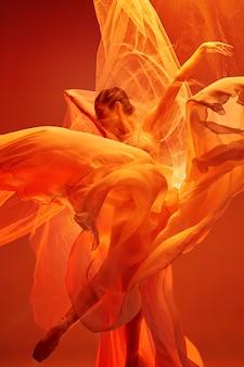 若い優雅な女性のバレエダンサーまたは赤いスタジオで踊る古典的なバレリーナ。トウシューズの白人モデル