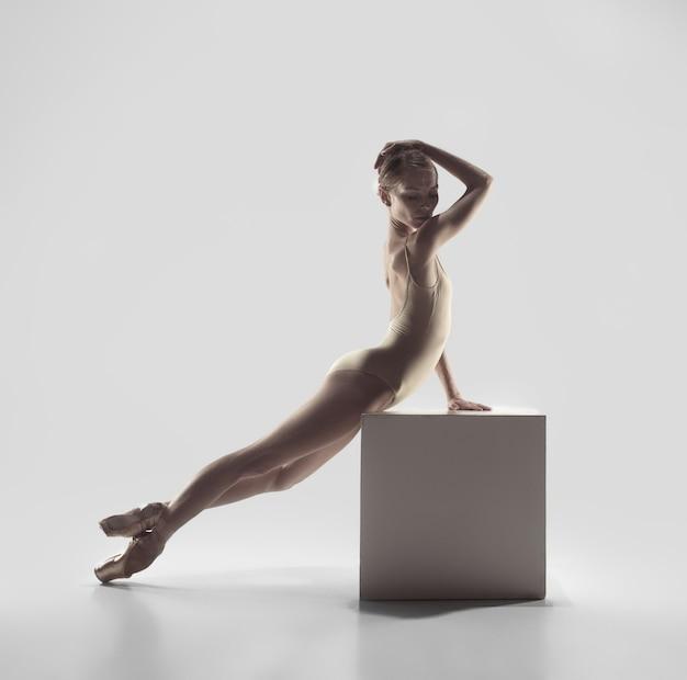 젊은 우아한 여성 발레 댄서 또는 흰색 스튜디오에서 춤을 추는 클래식 발레리나. 뾰족한 신발에 백인 모델