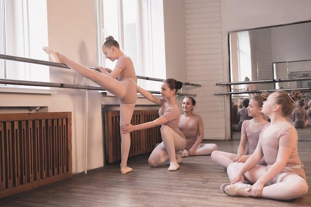 Young graceful female ballet dancers dancing at training studio