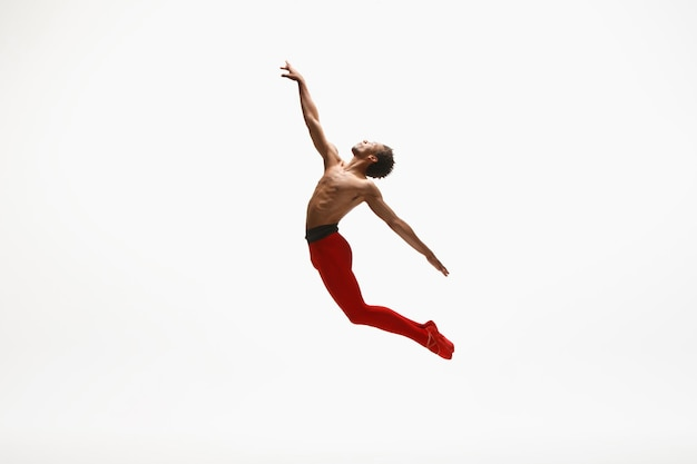 Young graceful male ballet dancer dancing on white studio background