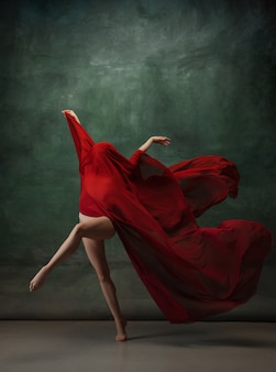 Young graceful tender ballerina on dark green studio space with red cloth