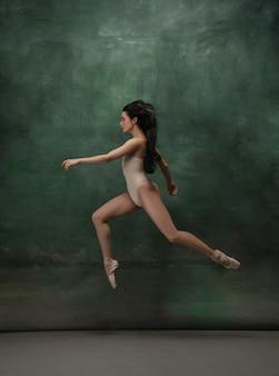 Young graceful tender ballerina on dark green studio space