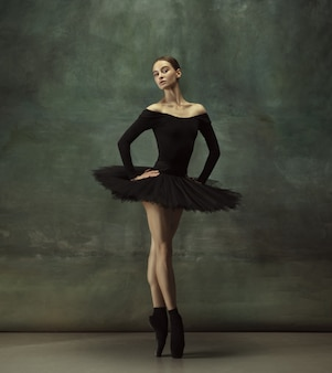 Young graceful tender ballerina on dark studio