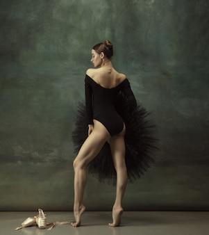 Young graceful tender ballerina on dark studio