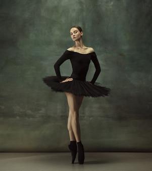 暗いスタジオで若い優雅な優しいバレリーナ