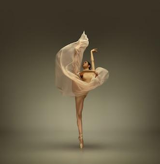 Молодая изящная нежная балерина на сером студийном фоне