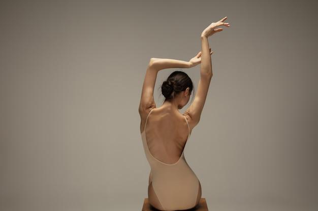 Молодая изящная нежная балерина на пастельной стене