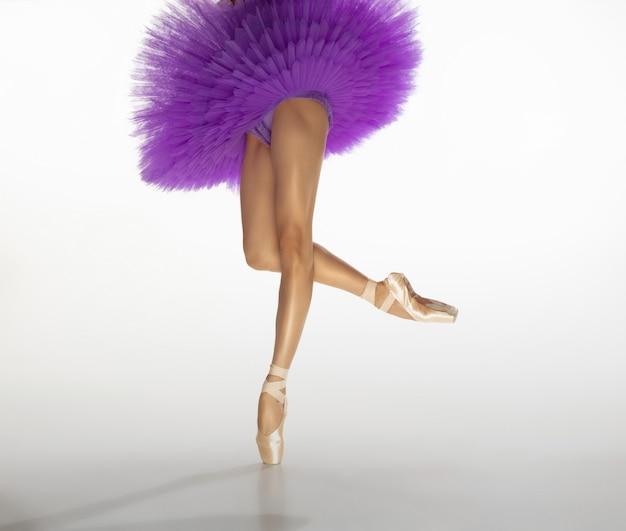 Giovane ballerina tenera graziosa sulla parete bianca