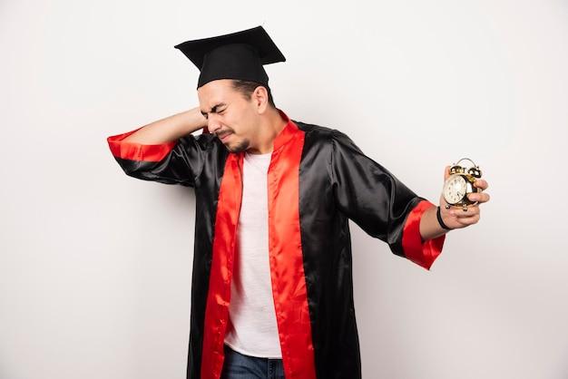 Молодой выпускник с часами, чувствуя боль на белом.