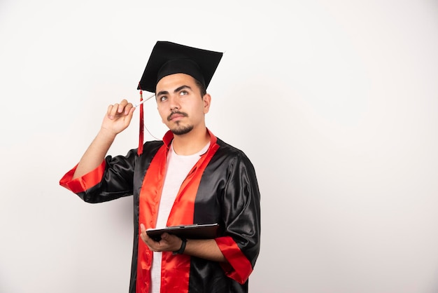 Young graduate student with diploma thinking on white.