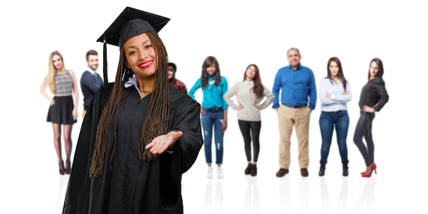 Young graduated black woman wearing braids reaching out to greet someone or gesturing to h