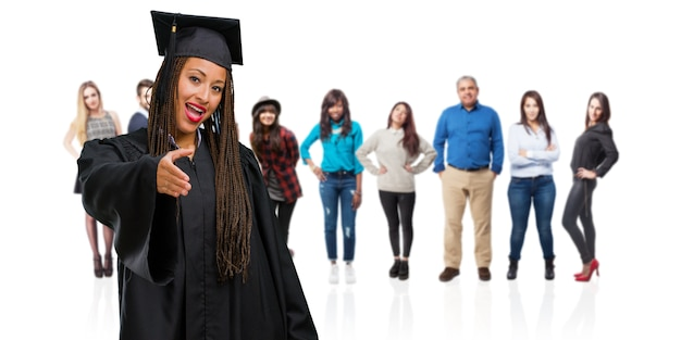 Young graduated black woman wearing braids reaching out to greet someone or gesturing to help, happy and excited