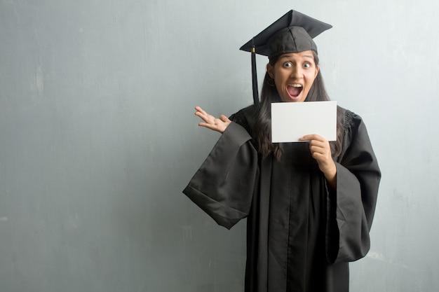 Молодой выпускник индийской женщины на стене кричать счастливым, удивленным предложением или pr
