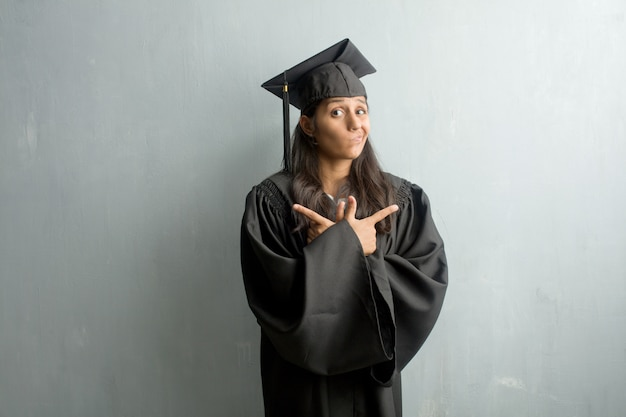 Young graduated indian woman against a wall confused and doubtful