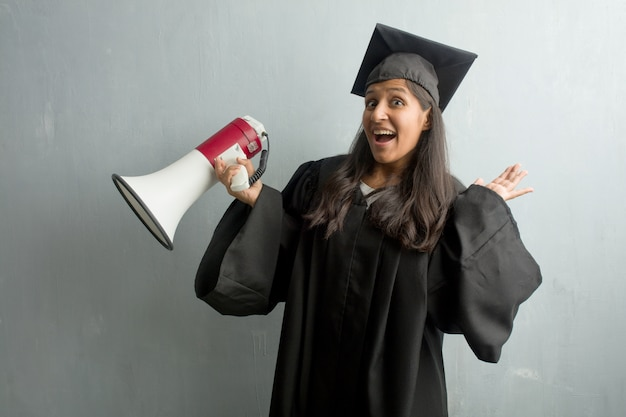 Young graduated indian woman against a wall crazy and desperate, screaming out of control