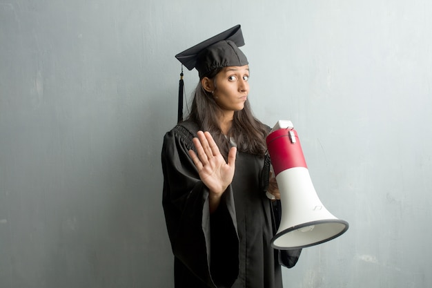 Young graduated indian woman against a wall tired and bored