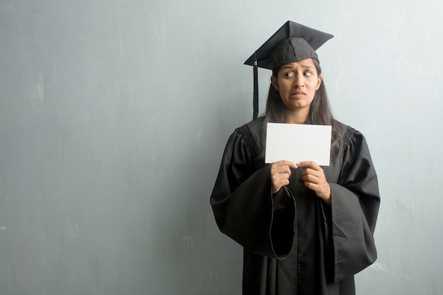 Young graduated indian woman against a wall very scared and afraid, desperate for something, cries of suffering and open eyes, concept of madness. holding a placard.