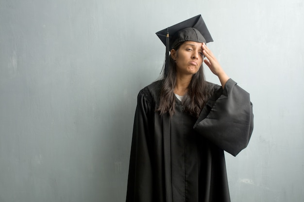 Young graduated indian woman against a wall worried and overwhelmed, forgetful, realize something, expression of shock at having made a mistake