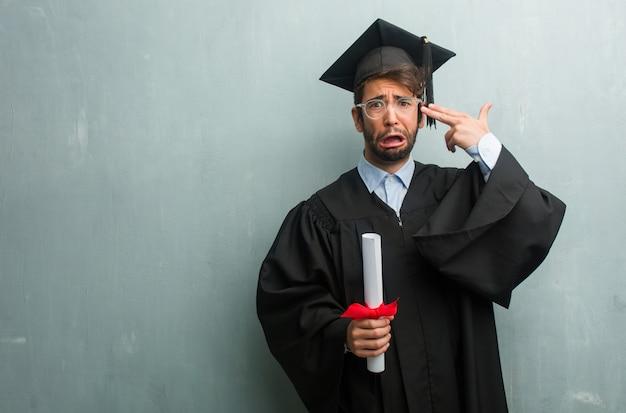 Молодой выпускник против стены гранж с копией пространства делает жест самоубийства, чувствуя грусть и испуг, образуя пистолет с пальцами