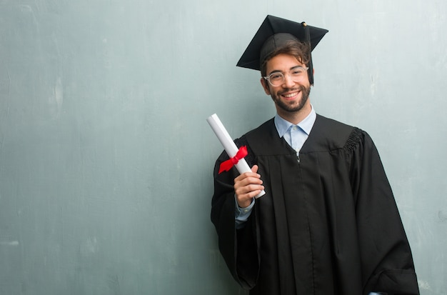 Young graduated man against a grunge wall with a copy space cheerful and with a big smile