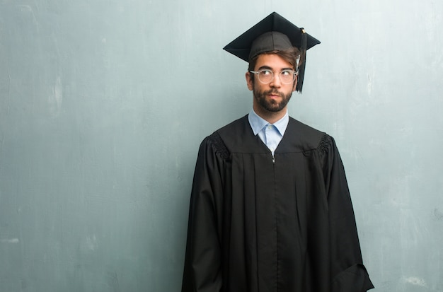 Young graduated man against a grunge wall with a copy space doubting and confused