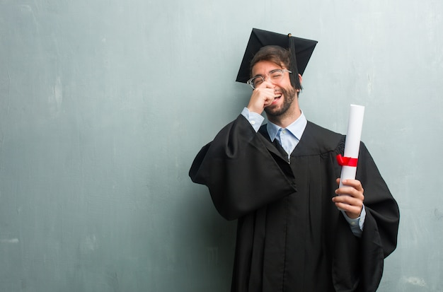 Young graduated man against a grunge wall with a copy space laughing and having fun, being relaxed and cheerful, feels confident and successful