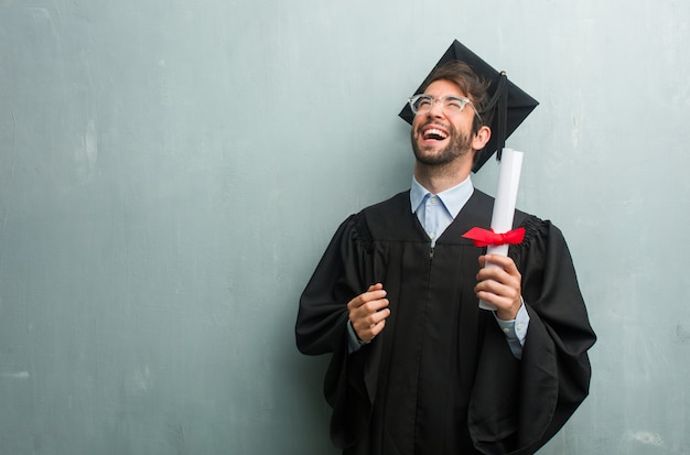 Young graduated man against a grunge wall with a copy space laughing and having fun