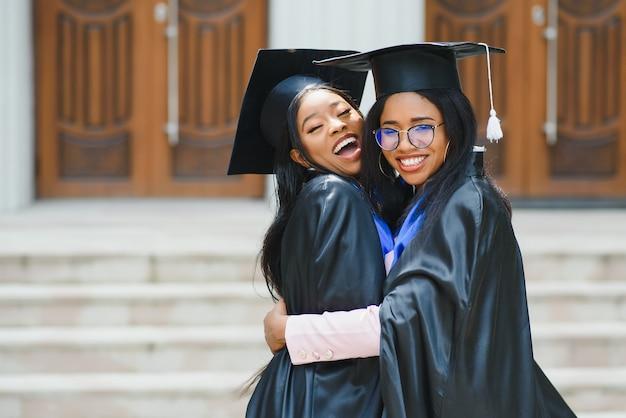 Молодые выпускники стоят перед зданием университета в день выпуска