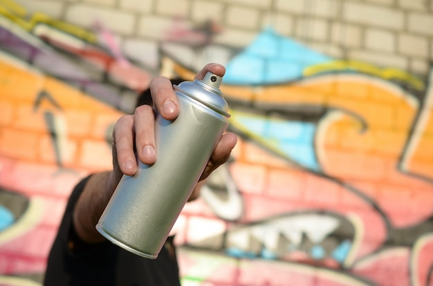 Young graffiti artist aims his spray can on background of colorful graffiti in pink tones