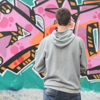 A young graffiti artist in a gray hoodie looks at the wall