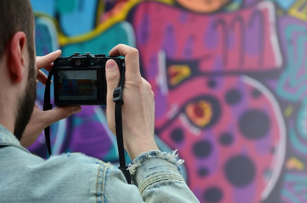 A young graffiti artist photographs his completed picture on